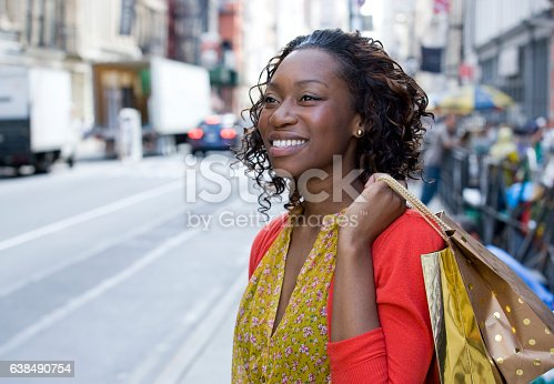 istock Young African American woman shopping in downtown city 638490754