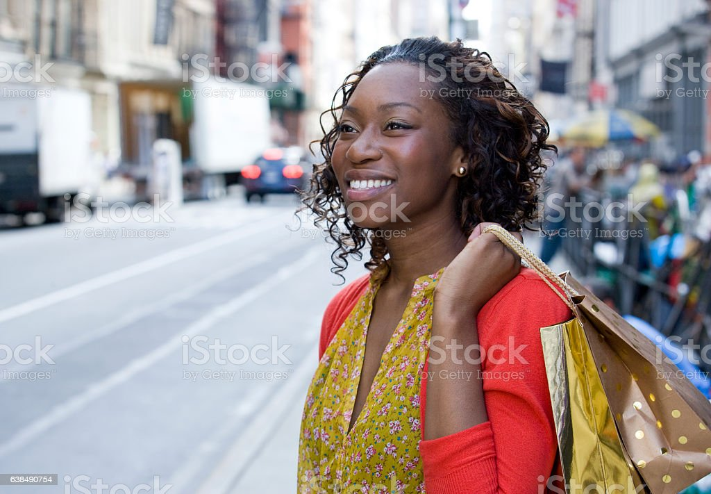 Young African American woman shopping in downtown city stock photo