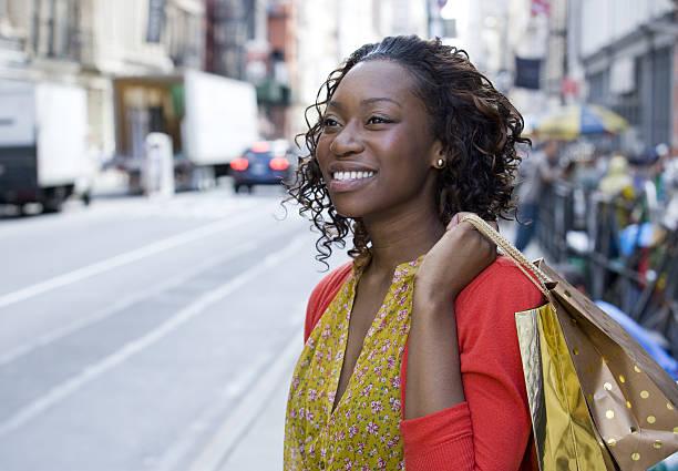 young african american woman shopping in downtown city - besondere geschenke stock-fotos und bilder