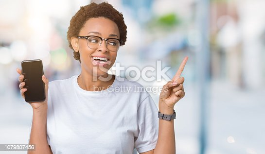 1159261513 istock photo Young african american woman showing smartphone screen over isolated background very happy pointing with hand and finger to the side 1079807456