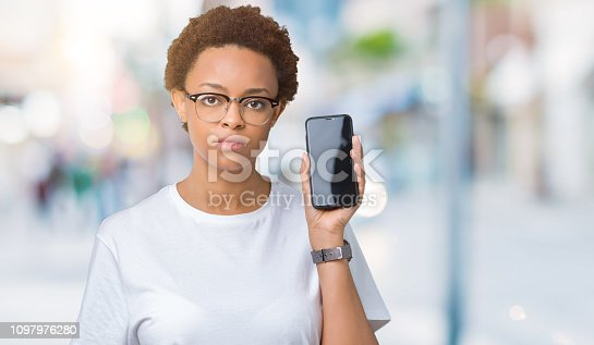 istock Young african american woman showing smartphone screen over isolated background with a confident expression on smart face thinking serious 1097976280
