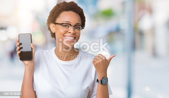 istock Young african american woman showing smartphone screen over isolated background pointing and showing with thumb up to the side with happy face smiling 1097976362