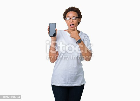istock Young african american woman showing smartphone screen over isolated background very happy pointing with hand and finger 1097980724