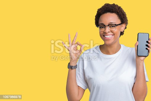 istock Young african american woman showing smartphone screen over isolated background doing ok sign with fingers, excellent symbol 1097986978