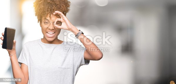 1159261513 istock photo Young african american woman showing smartphone screen over isolated background with happy face smiling doing ok sign with hand on eye looking through fingers 1098410516