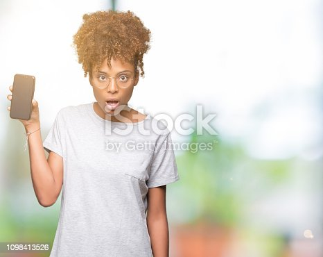 istock Young african american woman showing smartphone screen over isolated background scared in shock with a surprise face, afraid and excited with fear expression 1098413526