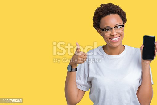 istock Young african american woman showing smartphone screen over isolated background happy with big smile doing ok sign, thumb up with fingers, excellent sign 1124765085