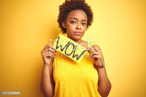istock Young african american woman showing wow banner board over yellow isolated background with a confident expression on smart face thinking serious 1212253562