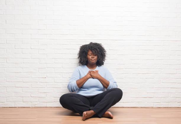 junge afrikanische amerikanische frau sitzen auf dem boden zu hause lächelnd mit händen auf brust mit geschlossenen augen und dankbar geste auf gesicht. gesundheitskonzept. - die wahrheit tut weh stock-fotos und bilder