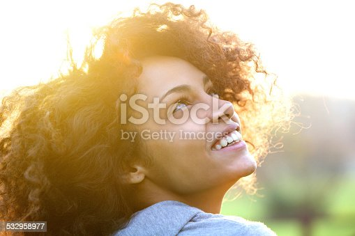 istock Young african american woman smiling and looking up 532958977