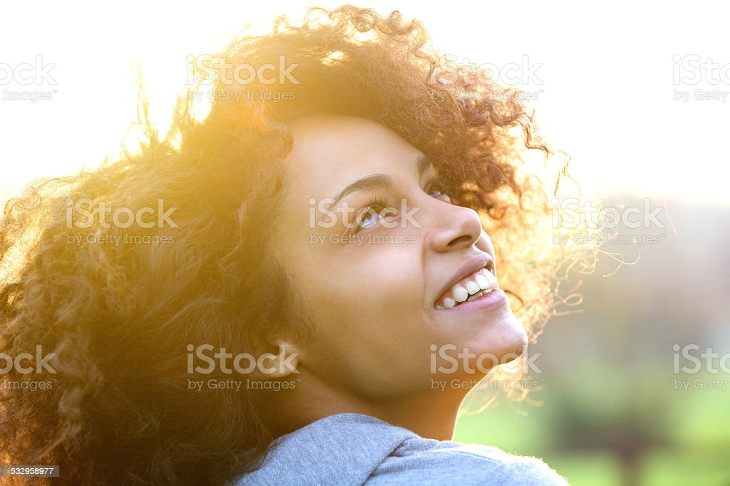 Young african american woman smiling and looking up stock photo