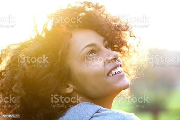 Photo of Young african american woman smiling and looking up