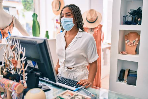 Young african american woman smiling happy working at the till wearing coronavirus safety mask at retail shop stock photo