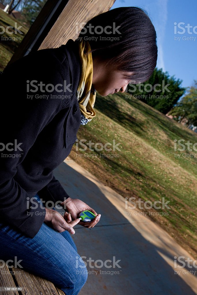 Young African American Woman Tests Her Blood Sugar royalty-free stock photo