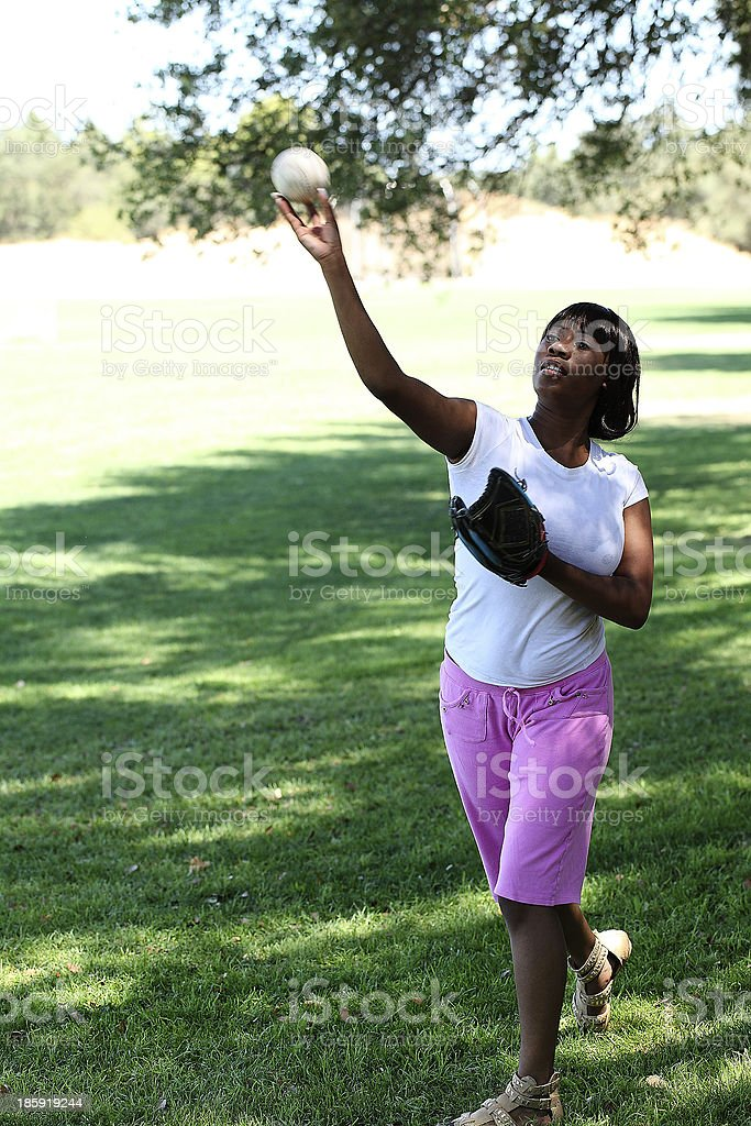 Young African American Woman Throwing baseball Park royalty-free stock photo