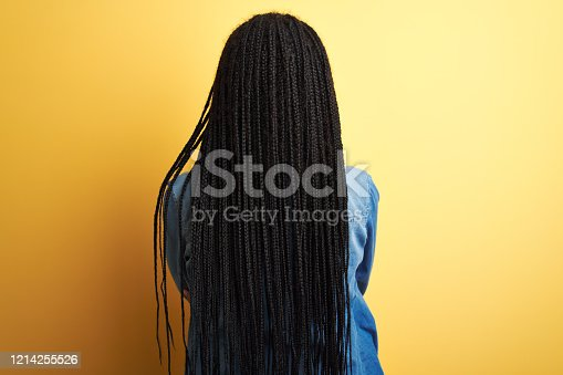 Young african american woman wearing denim shirt standing over isolated yellow background standing backwards looking away with crossed arms