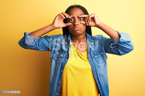 istock Young african american woman wearing denim shirt standing over isolated yellow background Trying to open eyes with fingers, sleepy and tired for morning fatigue 1174164343