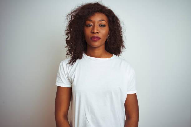 joven mujer afroamericana con camiseta de pie sobre fondo blanco aislado relajado con expresión seria en la cara. mirando la cámara de aspecto sencillo y natural. - black people fotografías e imágenes de stock