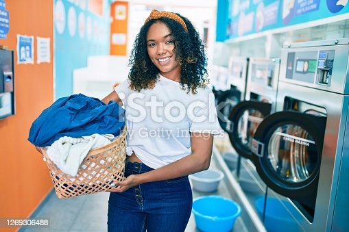 Young african american woman with curly hair smiling happy doing chores at the laundry
