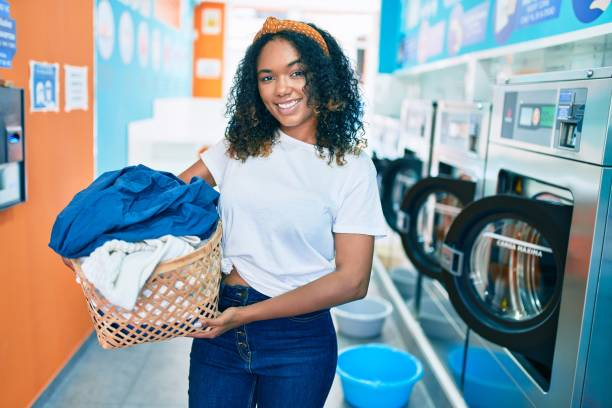 Young african american woman with curly hair smiling happy doing chores at the laundry stock photo