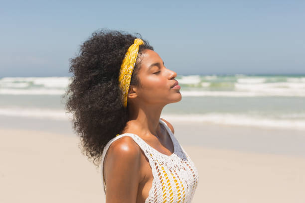 Young African American woman with eyes closed standing on beach stock photo
