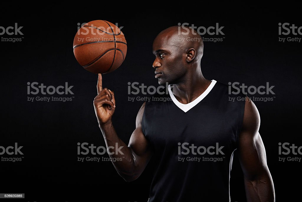 Young african athlete balancing basketball on his finger stock photo