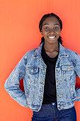 African Australian Teenage Girl Posing On Orange Wall In Denim Jacket