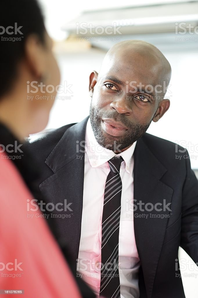Young African businessman listening intently to client stock photo