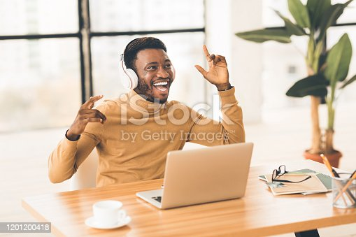 Life Is Good. Cheerful black student listening to favorite music in headphones at office, singing and dancing, free space