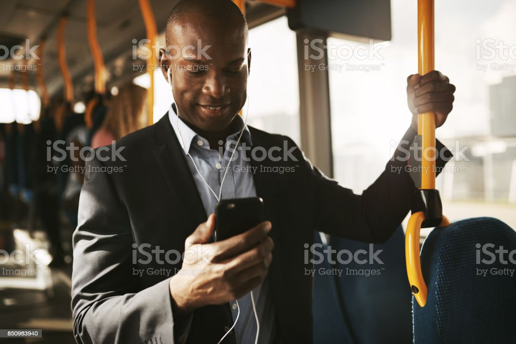Young African businessman riding on a bus listening to music stock photo