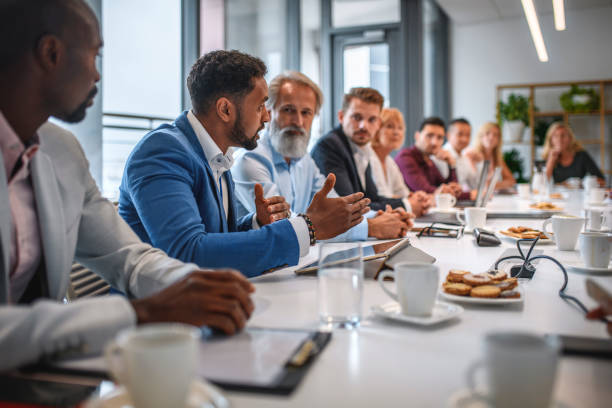 Young African Businessman Sharing Opinions at Meeting stock photo