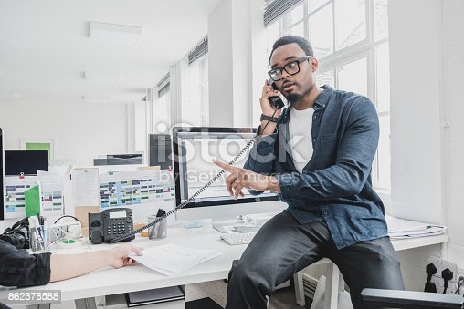 istock Young African businessman sitting on desk using phone and pointing 862378588