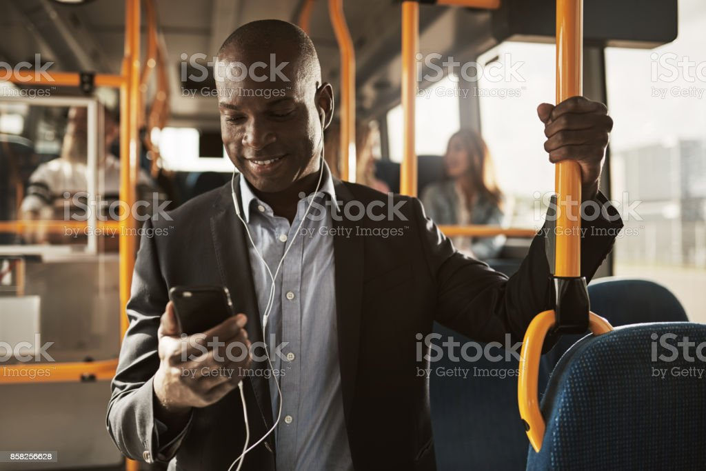 Young African businessman standing on a bus listening to music stock photo