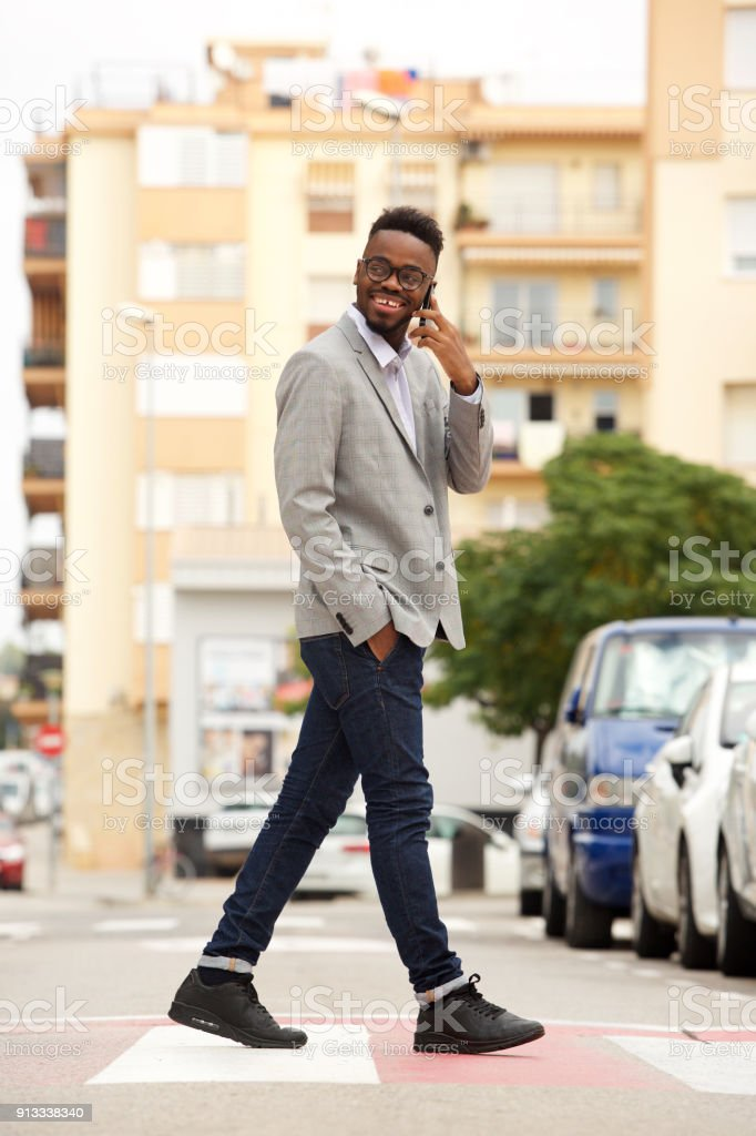 Full length side portrait of young african businessman walking and...