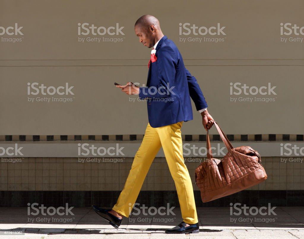 young african businessman walking Wirth bag and mobile phone stock photo