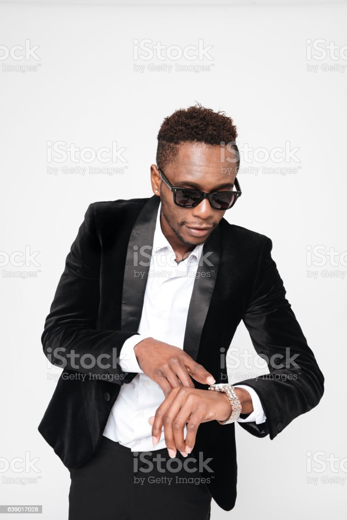 Young african businessman wearing glasses looking at watch stock photo