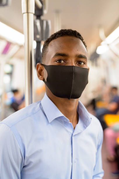 Young African businessman wearing mask and standing with distance inside train for protection from corona virus outbreak stock photo