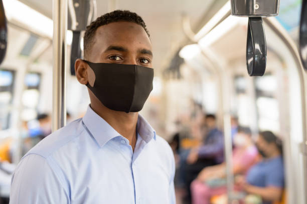 Young African businessman with mask for protection from corona virus outbreak standing with distance inside the train stock photo