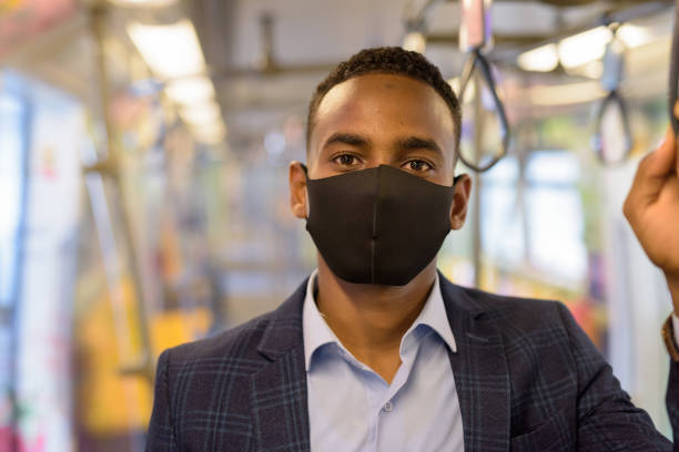 Young African businessman with mask for protection from corona virus outbreak riding with distance inside the train stock photo
