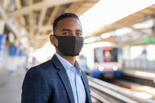 Young African businessman with mask for protection from corona virus outbreak thinking and waiting at sky train station stock photo
