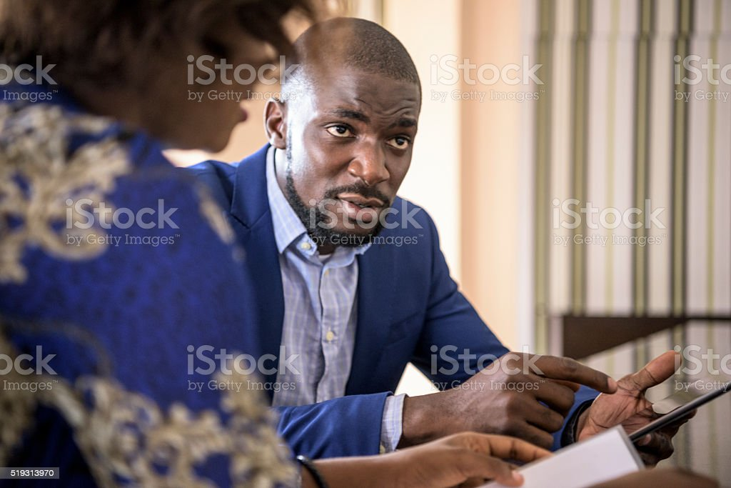 Young African businessman with tablet in meeting stock photo