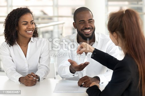istock Young african couple starting family life getting keys from realtor 1139630487