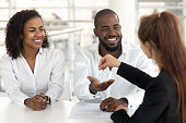 People sitting in modern office at desk, happy african couple receiving keys to their first home from woman real estate agent. Buy apartment, starting new life, tenancy renting, loan mortgage concept