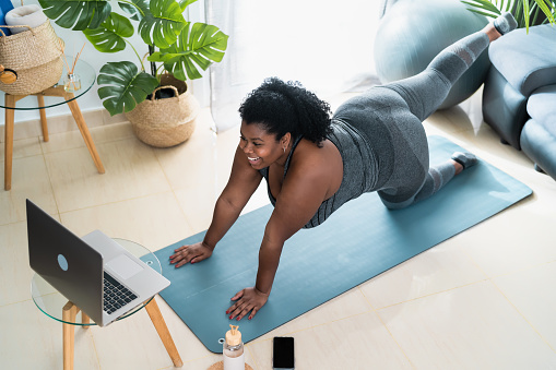 Young African curvy woman doing pilates virtual fitness class with laptop at home - Sport wellness people lifestyle concept