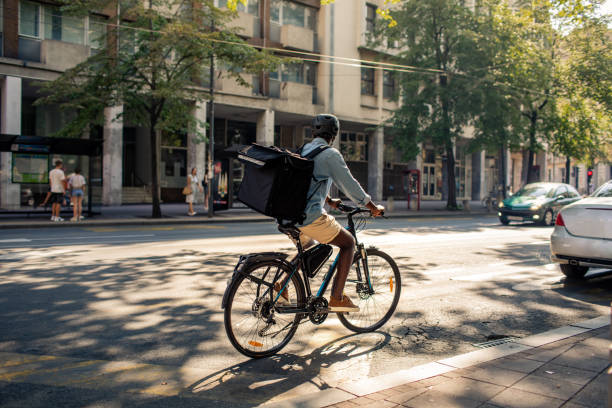 Young African Delivery Man Riding Bicycle In The City stock photo