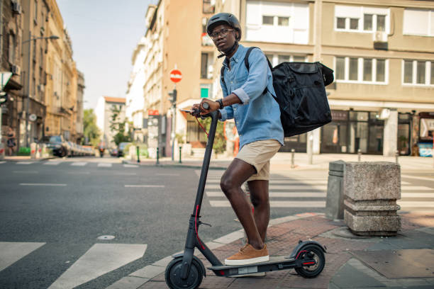 young african delivery man riding electric scooter in the city - side hustle stock pictures, royalty-free photos & images