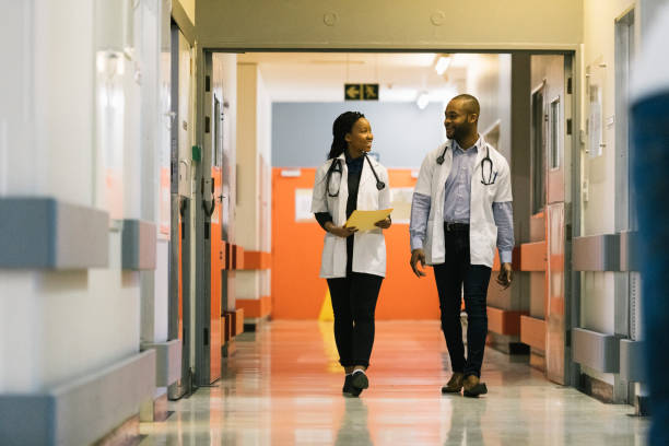 Young African doctors walking down hospital corridor talking stock photo