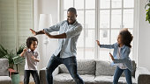 istock Young african ethnicity father teaches little kids to dance 1216562014
