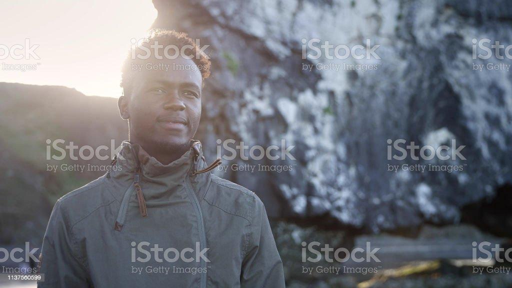 Handsome man enjoying black beach. Looking at view