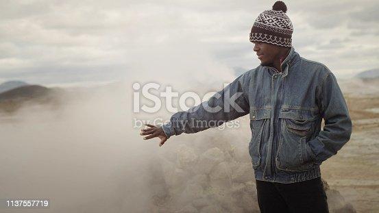 Sulfur rocks. Geothermal area. Man posing in steam